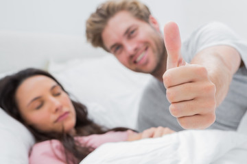 Man giving thumb up while his wife is sleeping