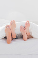 Couple crossing their feet under the duvet