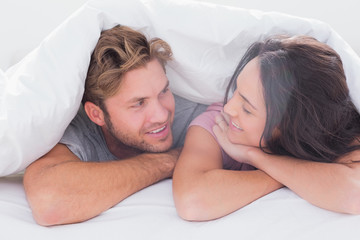 Couple under quilt smiling
