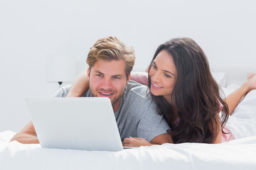 Woman embracing husband while using a laptop