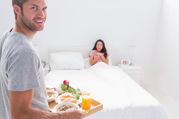 Handsome man bringing breakfast to his wife