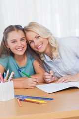 Mother helping daughter with homework in living room