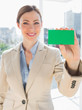 Smiling businesswoman holding up green business card