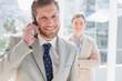 Businessman having phone conversation and smiling at camera