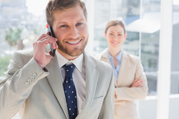 Businessman having phone conversation and smiling at camera