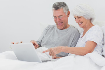 Mature man with wife pointing at a laptop