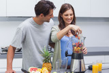 Couple putting fruits into blender
