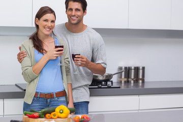 Delighted couple clinking their glasses of red wine