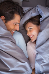 Lovely couple having fun wrapped in their blanket