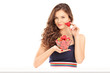 Beautiful young woman holding a bowl of strawberries