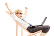 Excited man with laptop sitting on a beach chair