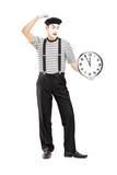 Full length portrait of a mimic holding a clock and thinking