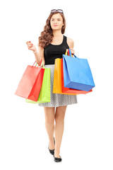 Full length portrait of a young woman walking with shopping bags