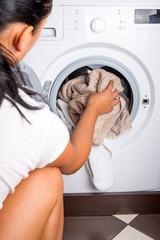 Woman loading laundry to the washing machine