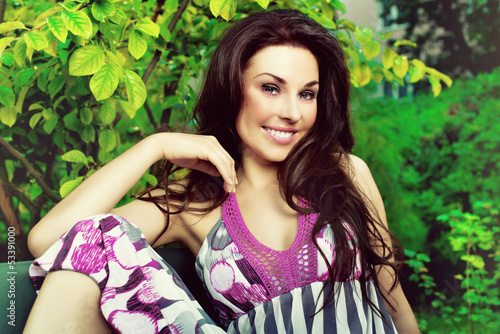 beautiful woman smiling and sitting on a bench in the park