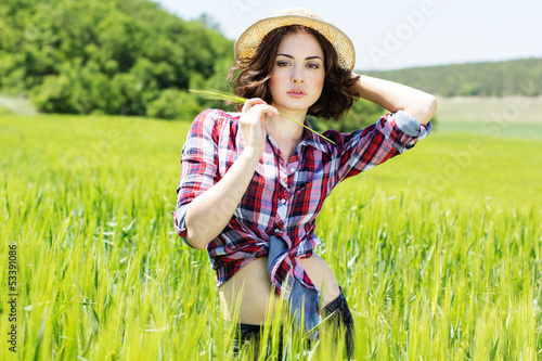 Beautiful  woman in hat on summer meadow