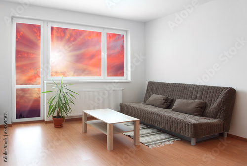 Living room interior with sunset view.