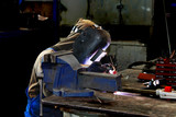 Welder working in production workshop on a workbench poster
