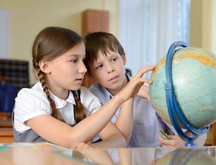 Two shcoolchildren looking at globe