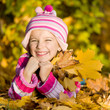 smiling girl lie on the autumn leaves