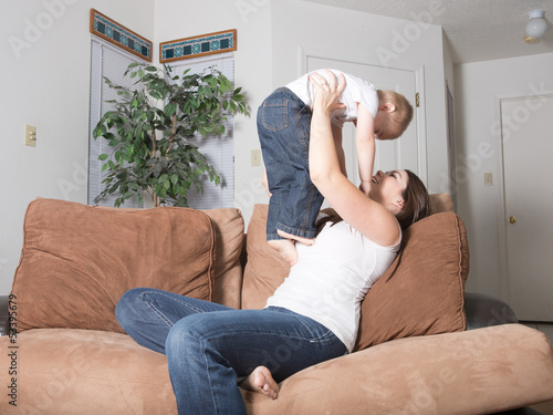 Young mother and son engaging in play at home together