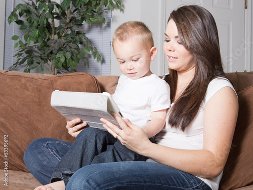 Young mother and toddler son reading together