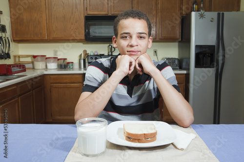 Mixed ethnicity teenager eating peanut butter jelly sandwich