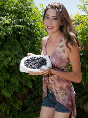 Pretty casual woman holding bowl of blueberries outside