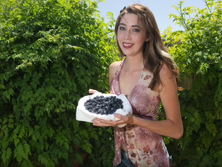 Enthusiastic young woman holding a bowl of blueberries outdoors