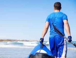young man holding kayak at shore beach