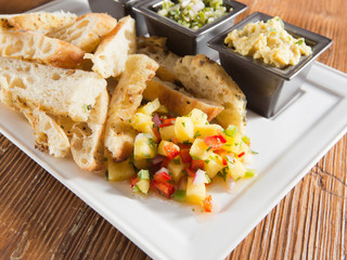 tray of toasted artisan bread, salsa and fresh dips