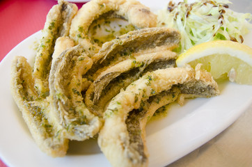 Spider fish fillets coated with salad and lemon.(Trachinus)