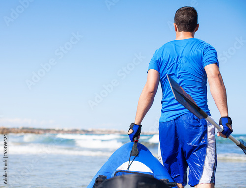 young man holding kayak at shore beach