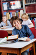 Happy Schoolboy Giving Book While Sitting At Table In Library