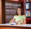 Happy Schoolgirl With Book Sitting At Table In Library