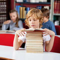 Schoolboy With Stack Of Books Reading At Table In Library