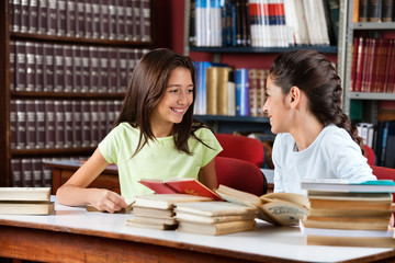 Schoolgirls Looking At Each Other While Studying In Library