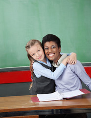 Schoolgirl Hugging Professor At Desk