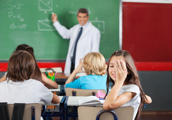 Girl Covering One Eye While Sitting At Desk In Classroom