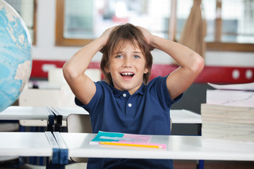 Shocked Little Boy With Globe And Books At Desk