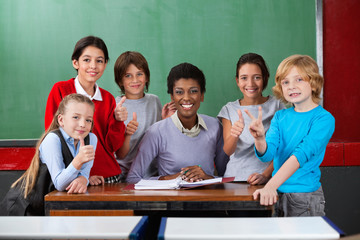 Happy Teacher And Schoolchildren Gesturing Together At Desk