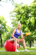 Beautiful woman exercising in a park with a ball and dumbbell