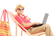 Mature male tourist on a sun lounger with a laptop