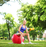 Young woman exercising with a dumbbell and pilates ball in a par