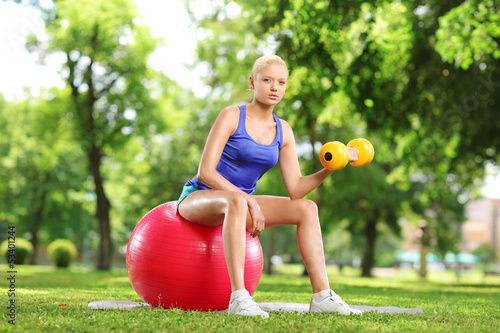 Female lifting weigth and sitting on an exercise ball in park