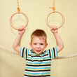 Little child playing sports on gymnastic rings