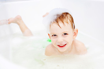 little boy swimming in bath and smiling