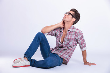 casual man poses on the floor and looks up