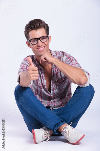 casual man sits and shows thumbs up