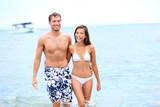 Beach couple in love walking happy in water